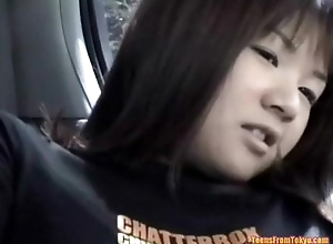 An Asian girl is sitting on the back seat of a car.  from http://alljapanese.net